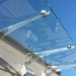tettoia in vetro fissata con staffe in acciaio verniciata a specchio