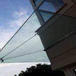 tettoia in vetro fissata con tiranti e pinze in acciaio inox