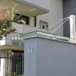 tettoia in vetro su ingresso pedonale fissata con tiranti in acciaio